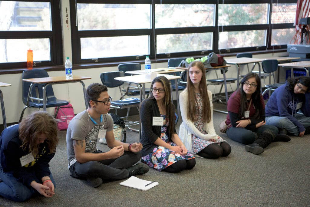 Teens sitting in a circle talking.