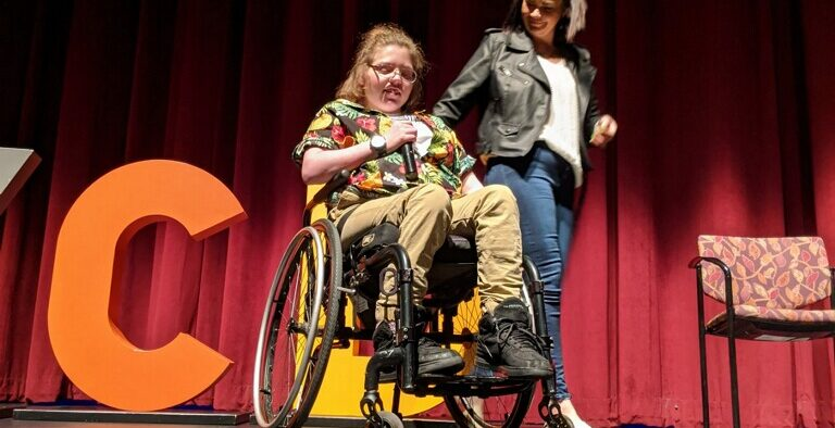 A student in a wheelchair with a helper behind her.