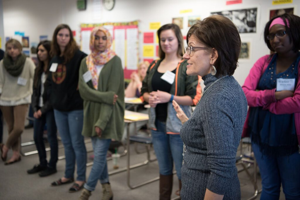 Students stand in a circle listening to a workshop presenter.