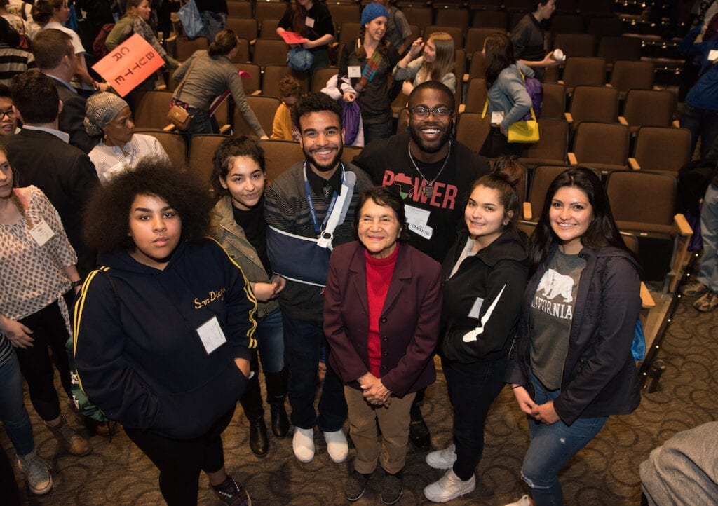 Dolores Huerta standing beside students.